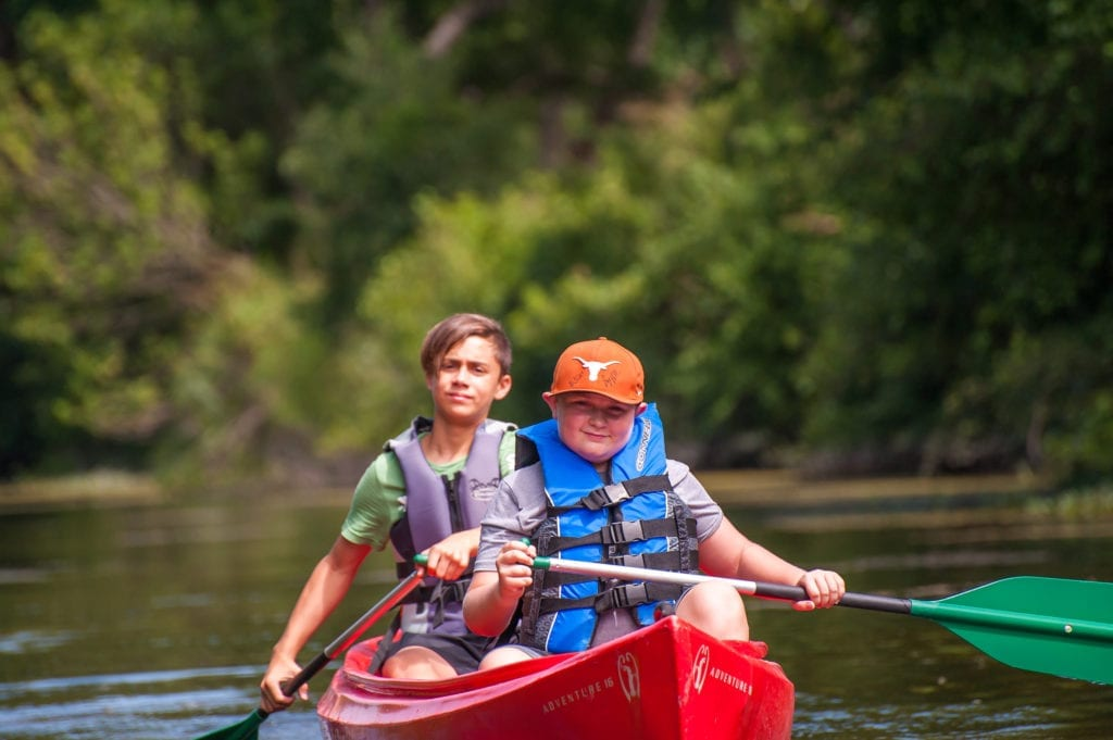 2 kids canoeing and enjoying the benefits of nature at YMCA Camp Moody