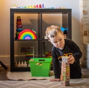 A little boy loves to play in his Montessori Home Learning Area